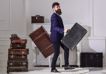 Man, traveller with beard and mustache with luggage, luxury white interior background. Macho elegant on cheerful face walks near pile of vintage suitcase, holds suitcases. Hotel service concept.
