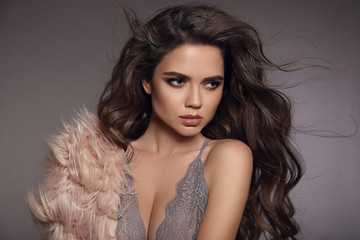 Sexy brunette in gray lace lingerie. Fashion studio portrait of beautiful girl with long curly hair and evening makeup wearing in pink fur coat. Vogue style model over studio background.