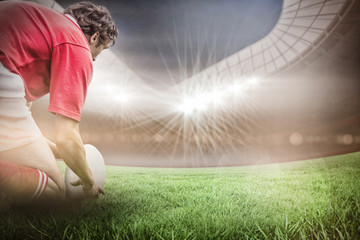 Rugby stadium against rugby player getting ready to kick ball