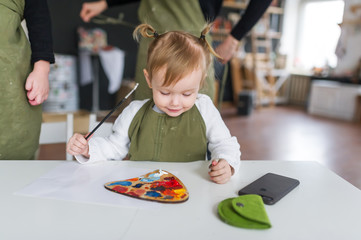Little caucasian girl painting with paintbrush and colorful paints.
