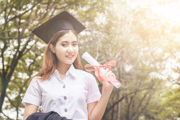 happy graduate showing certificated in hand with sky background.color tone