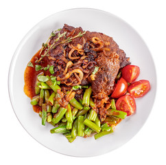 Roast beef with onion and green beans on plate isolated on white top view