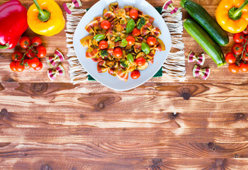 Italian pasta farfalle in tomato sauce and various type of vegetables on a wooden background, free space for text.