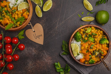 Vegan Sweet Potato Chickpea curry in wooden bowl on a dark background, top view, copy space. Healthy vegan food concept.