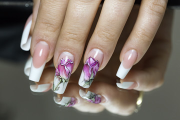 Beautiful multicolored flowers on a transparent lacquer on the nails