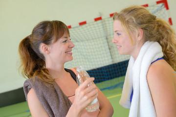 Young women drinking water on handball court