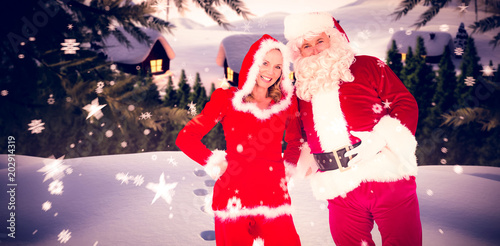 Santa And Mrs Claus Smiling At Camera Against Cute Village In The Snow