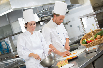 two chefs preparing in a restaurant kitchen