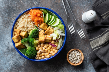 Colorful Buddha bowl on dark background, top view. Buddha bowl with quinoa, tofu, broccoli, sweet potato, chickpea and cucumber. Healthy vegetarian salad bowl