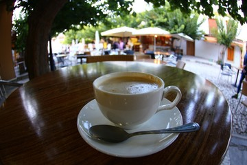 Cup of coffee on a table with olive tree, with the sea view and sky in protaras, cyprus island.