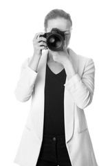 Woman photographer taking images with dslr camera isolated on white background. Black and white image.