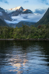 Mountain and glacier reflected in the water at sunset in beautiful Harrison Cove at Milford Sound, Fiordland National Park, New Zealand South Island.