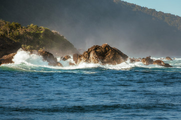 Spectacular Waves crashing on the seashore of Tasman Sea at Milford Sound in New Zealand.