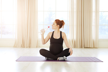 Pregnant woman sitting in yoga pose with a bottle of water