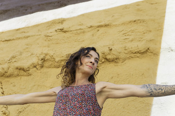 Tattooed woman in front of a painted wall