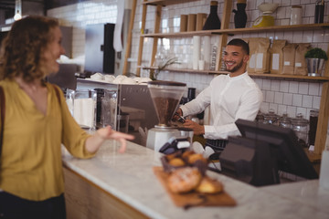 Smiling waiter looking at female customer standing at counter