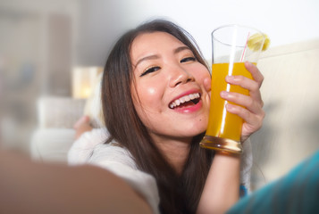 close up face portrait of young beautiful and happy Asian Chinese woman taking selfie picture with mobile phone drinking orange juice at home