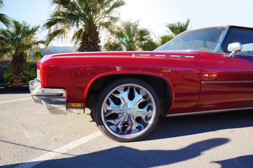 Red luxury car with chrome-plated discs against the backdrop of palm trees