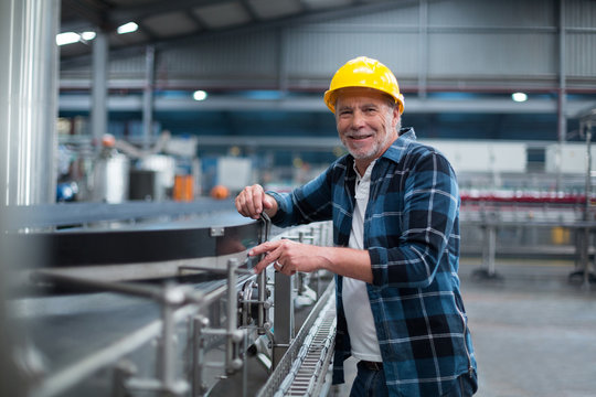 Portrait of smiling factory worker near production line