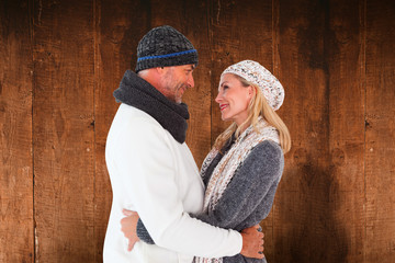 Happy couple in winter fashion embracing against weathered oak floor boards background