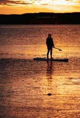 Sup boarding under sunset lake