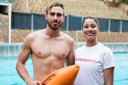 Two smiling lifeguards standing at poolside