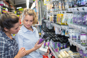 beautiful female friends shopping for diy tools at hardware store