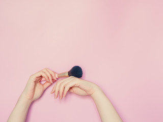 cosmetic and beauty concept from beauty asian hand hold and use cosmetic brush paint on hand with isolated pink pastel background