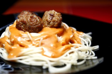 Spaghetti pasta dish topped with fried meatballs