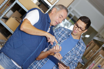 Two men in stores looking at object held in palm of hand