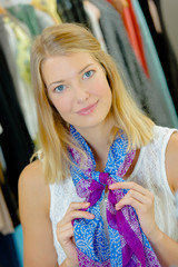 Young woman trying a scarf on