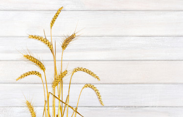 Ears wheat on background of white painted wooden planks with space for text.Top view, flat lay.