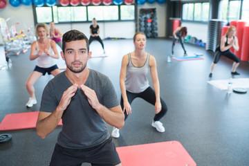 aerobics group members doing squat