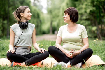 Young and elder woman doing yoga in the park