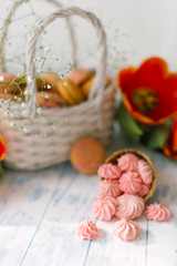Blossoming tulips near a basket with macaroons