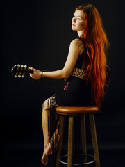 Beautiful redhead woman playing acoustic guitar