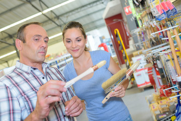 Couple choosing paint brushes in hardware store