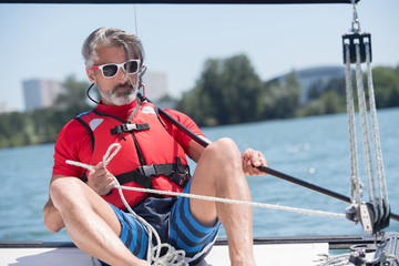man sailing boat on lake