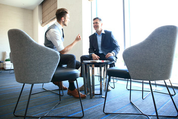 Mature businessman using a digital tablet to discuss information with a younger colleague in a modern business lounge.