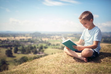 Boy sitting on a hill reading a book in a meadow