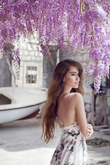 Beautiful young woman portrait over wisteria blossom. Attractive brunette girl with long healthy hair in white dress dreaming.