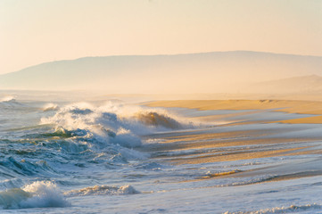 Mediterranean cost ar sunset. Tropical island shore with strong stormy waves in motion. Sunlight on yellow sand beyond ocean. Paradise picturesque seascape. Beautiful nature seaside landscape.  Relax.