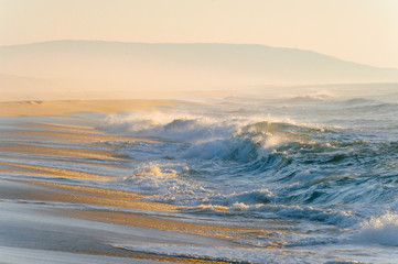 Mediterranean cost ar sunset. Tropical island shore with strong stormy waves in motion. Sunlight on yellow sand beyond ocean. Paradise picturesque seascape. Beautiful nature seaside landscape.  Relax. Fototapete