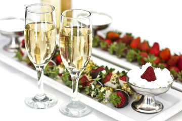 Fresh strawberries in chocolate with whipped cream and champagne in glasses