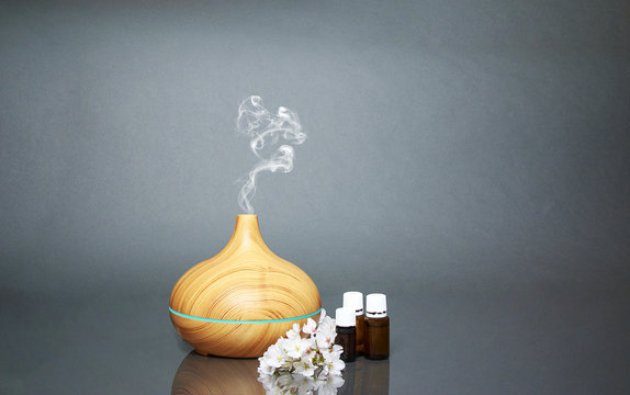 Electric Essential oils Aroma diffuser, oil bottles and flowers on gray surface with reflection