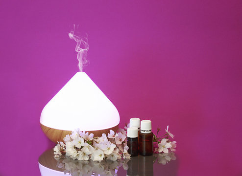Electric Essential oils Aroma diffuser, oil bottles and flowers on pink surface with reflection