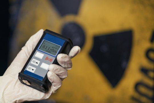 Radiation supervisor in glove with geiger counter checks the level of radiation