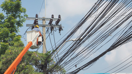 Asian worker to change new electricity pole in the cable car has copy space
