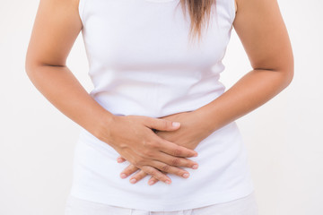 Young beautiful woman having painful stomachache on white background.Chronic gastritis. Abdomen bloating concept.
