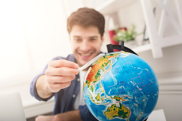 Man dreaming about travel, looking at globe